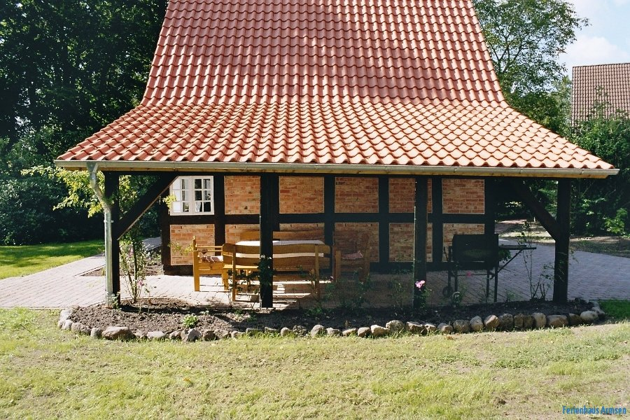 Überdachte Terrasse mit Gartenmöbel und Grill